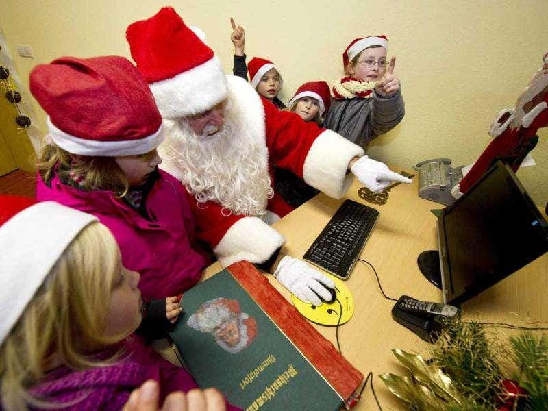 A man dressed up as Santa Claus sits at a desk with a computer in the Santa Claus post office in the Eastern German town of Himmelpfort (Heaven's Gate). Children can send their Christmas wish lists to Himmelpfort from around the world and receive a reply from Santa. AFP Photo / John Macdougall