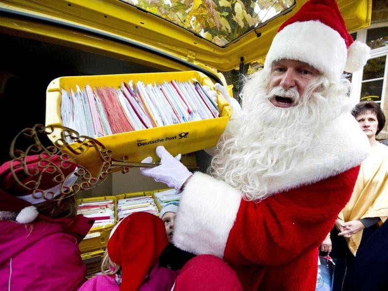 A man dressed up as Santa Claus holds up a box full of letters in front of the Santa Claus post office in the Eastern German town of Himmelpfort (Heaven's Gate). Children can send their Christmas wish lists to Himmelpfort from around the world and receive a reply from Santa. AFP Photo / John Macdougall