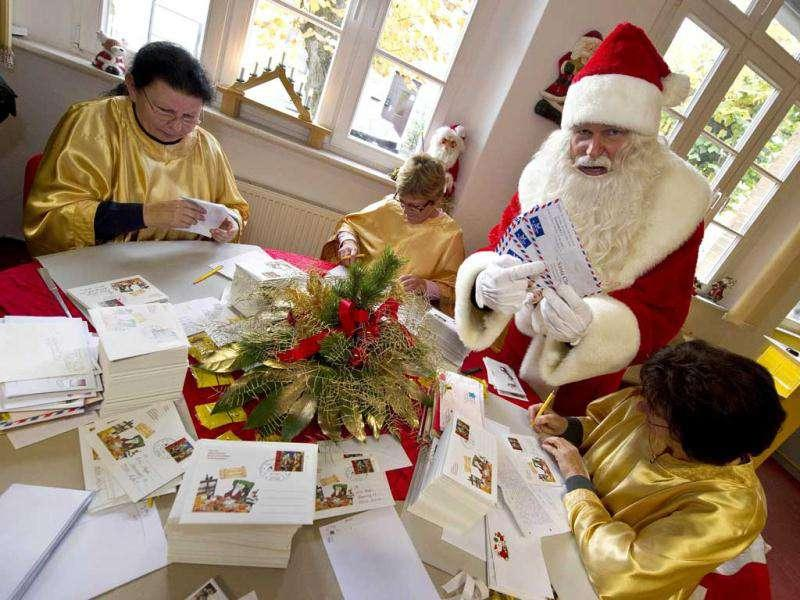 A man dressed as Santa Claus poses with his 'helpers' who are busy answering children's letters in the Santa Claus post office in the Eastern German town of Himmelpfort (Heaven's Gate). Children can send their Christmas wish lists to Himmelpfort from around the world and receive a reply from Santa. AFP Photo / John Macdougall