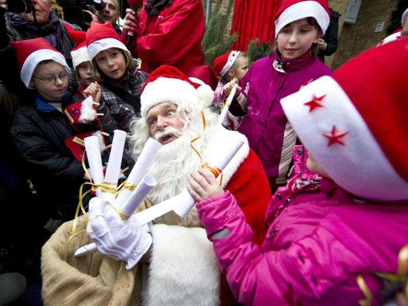 A man dressed up as Santa Claus is surrounded by local children giving him their Christmas wish lists as he arrives at the Santa Claus post office in the Eastern German town of Himmelpfort (Heaven's Gate). Children can send their Christmas wish lists to Himmelpfort from around the world and receive a reply from Santa. AFP Photo / John Macdougall