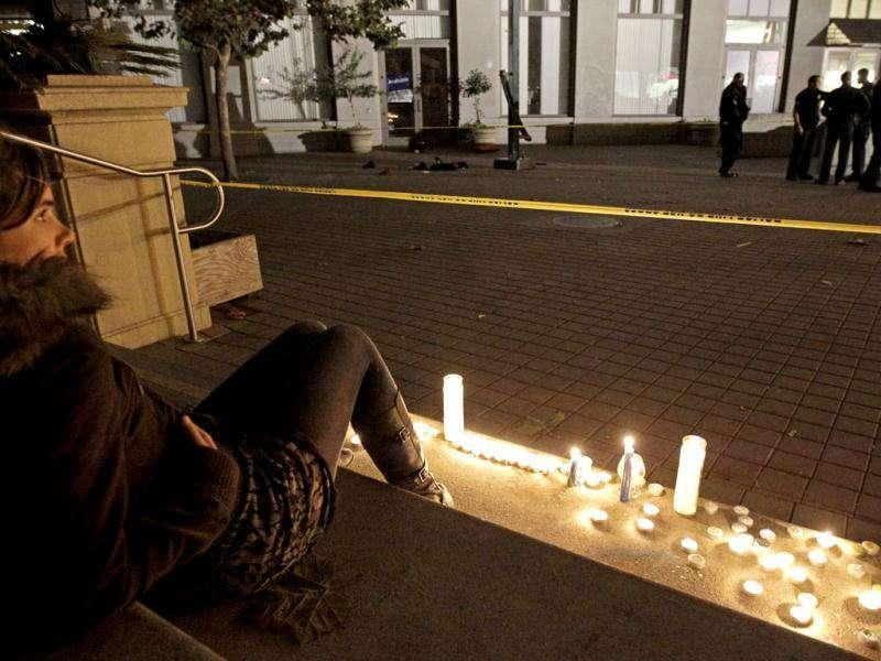 An Occupy Oakland protestor sits beside candles at the scene of a shooting on Thursday, in Oakland, Calif. AP