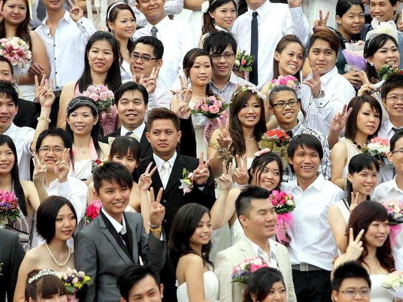 Newlywed couples pose for photographs during a mass wedding ceremony at the Thean Hou temple in Kuala Lumpur. AFP