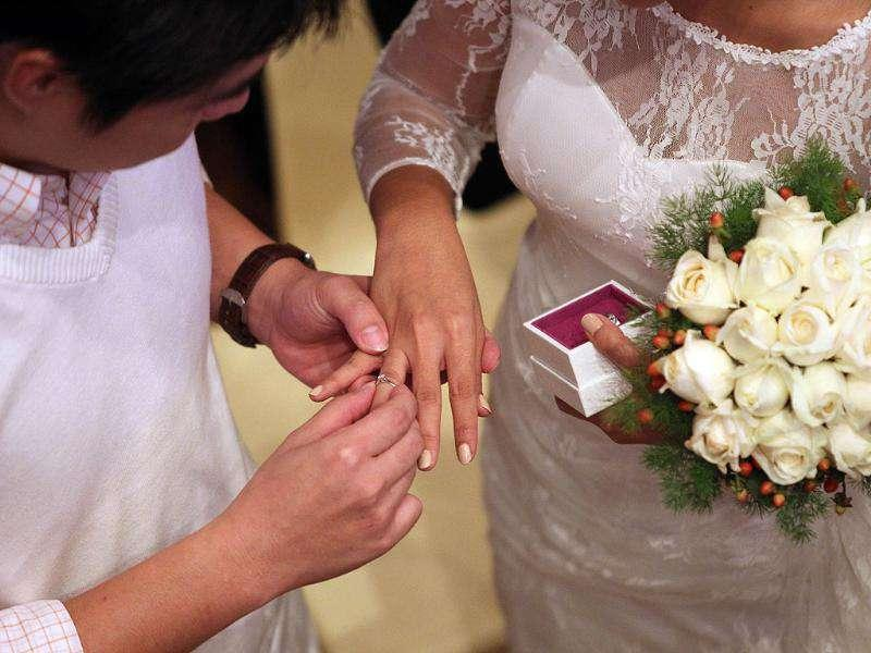 A couple exchanges rings during a mass wedding ceremony at the Thean Hou temple in Kuala Lumpur on 11.11.11. (Photo: AFP)