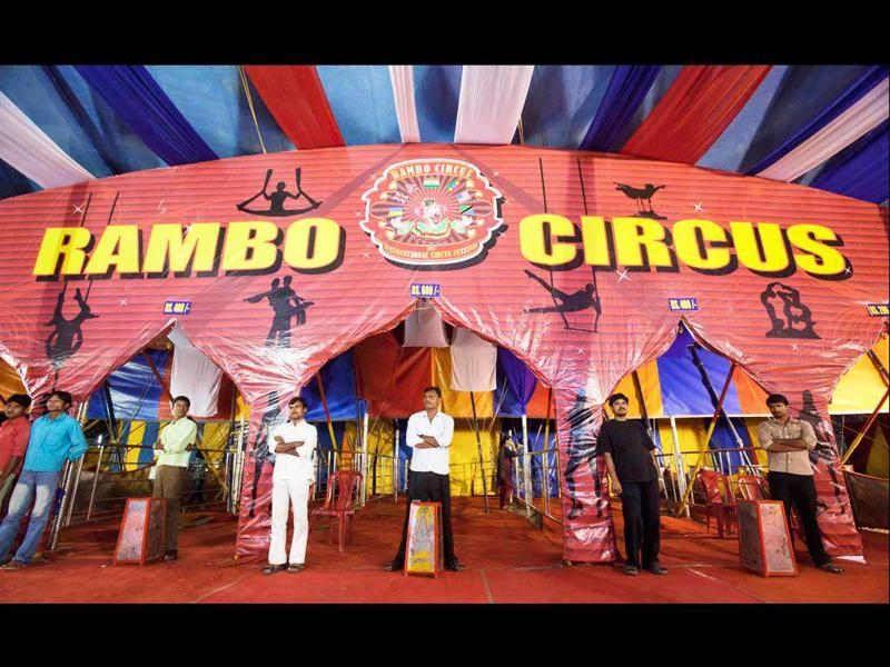 Ushers stand at the entrance to the Rambo Circus in Mumbai.