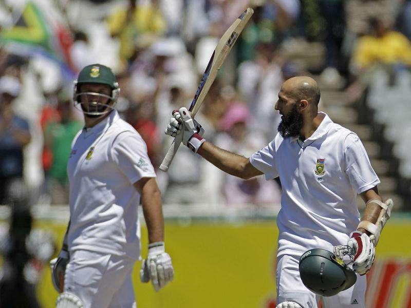 South Africa's Hashim Amla, right, holds up his bat after scoring a century during a cricket Test match against Australia in Cape Town, South Africa.
