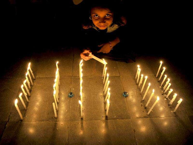 Young girl Mahima poses as she lights a series of candles forming the