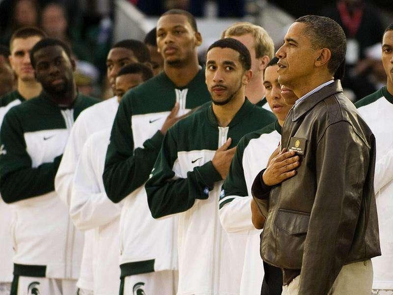 Barack Obama and Michelle Obama stand next to the Michigan State Spartans during the United States National Anthem before the start of the NCAA men's college basketball Carrier Classic between the Spartans and the North Carolina Tar Heels. Getty Images/AFP