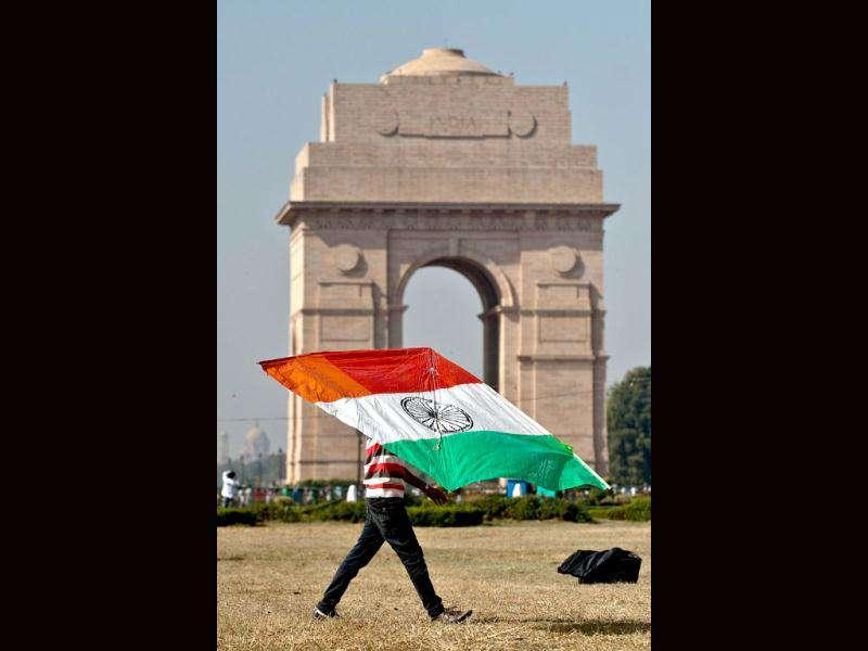 A man carries a kite in the colours of the Indian national flag during a kite-flying festival on the lawns of the India Gate monument in New Delhi. (AFP Photo/ Manan Vatsyayana)