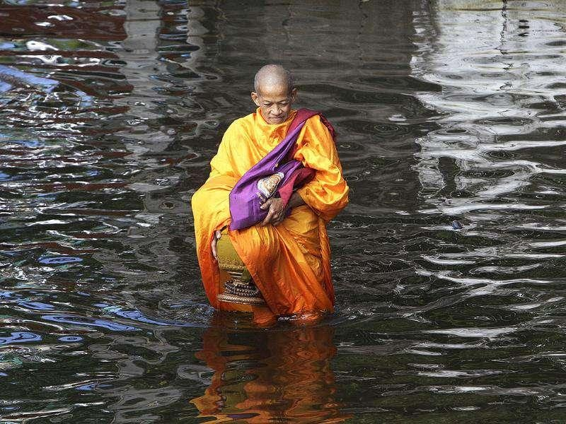 A Thai Buddhist monk, holding a bowl for morning alms, wades through floodwaters on Phisi Charoen district in Bangkok, Thailand. (AP Photo/Sakchai Lalit)
