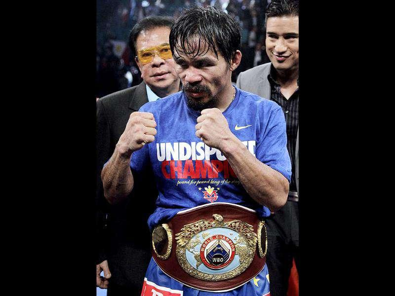 Manny Pacquiao, of the Philippines, poses with his championship belt after defeating Mexico's Juan Manuel Marquez during a WBO welterweight title fight in Las Vegas. (AP Photo/Julie Jacobson)
