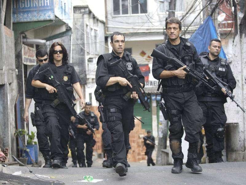 Brazil's policemen guard the streets of the Rocinha slum in Rio de Janeiro. Elite police units backed by armoured military vehicles and helicopters invaded the largest slum in this seaside Olympic city before dawn. It's the most ambitious attempt yet to bring security to a town long known for its violence.