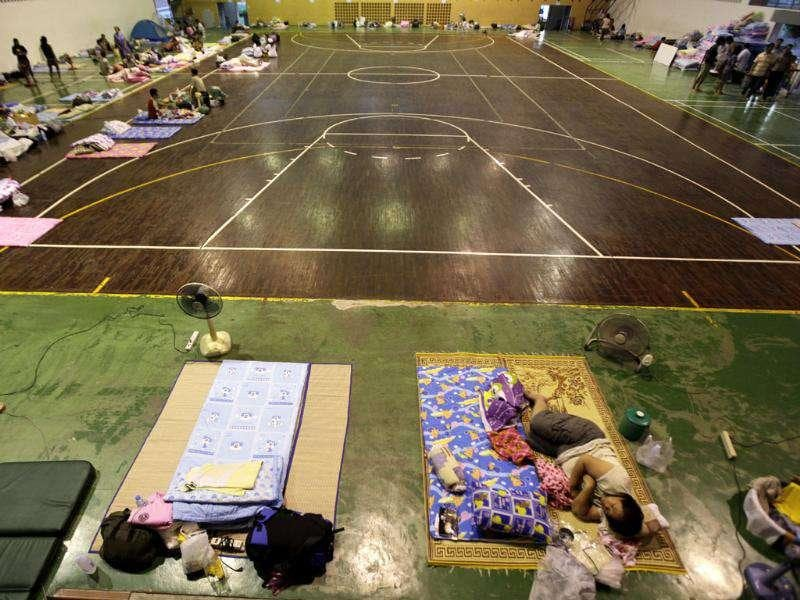 Evacuees from flood hit areas take shelter at a basketball court of a school used as a makeshift relief center in Bangkok, Thailand.