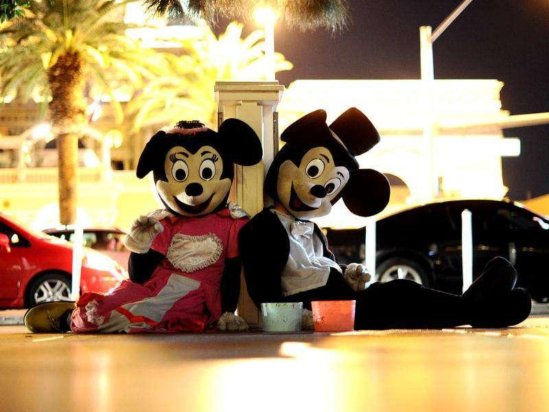 Two persons dressed as Mickey and Minnie mouse wait to get some tips along the Las Vegas Strip in Las Vegas.