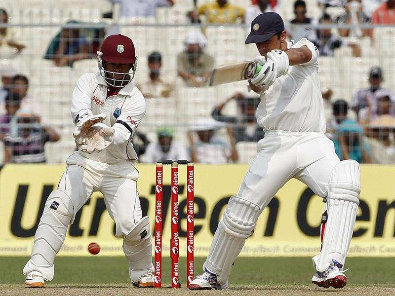 Rahul Dravid (R) plays a shot as West Indies' wicketkeeper Carlton Baugh watches on the first day of their second Test cricket match in Kolkata.