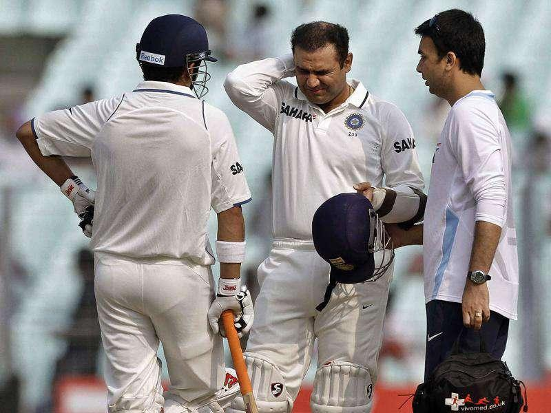 Virender Sehwag (C) grimaces in pain as he receives treatment after being hit by a ball during the second Test cricket match in Kolkata.