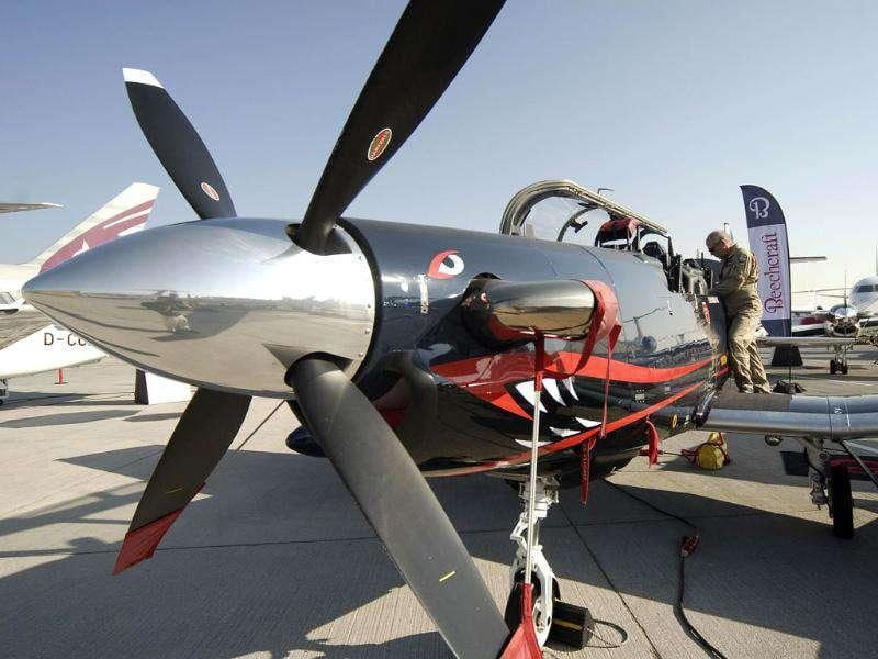 A pilot stands by his plane, a Hawker Beechcraft T-6C Texan II, during the second day of the Dubai Airshow.