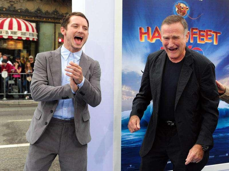 Actors Elijah Wood and Robin Williams laugh as they arrive at the premiere of Happy Feet Two.