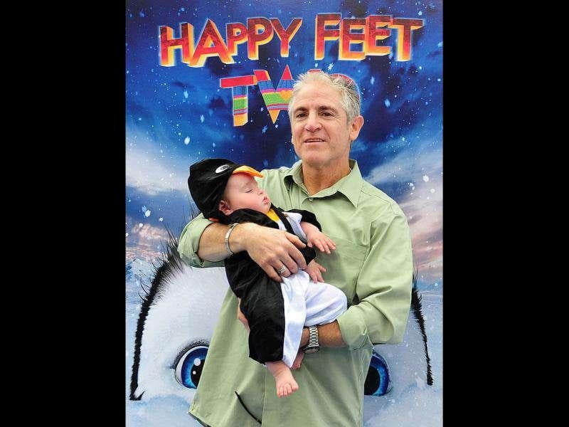 Actor Carlos Alazraqui holds baby Riley at the world premiere of Happy Feet Two.