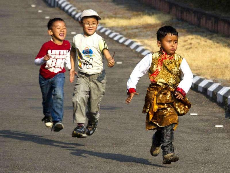 Tibetan children pursue another child in a Tibetan traditional dress as they arrive to welcome the Dalai Lama at the Kangra airport near Dharmsala.