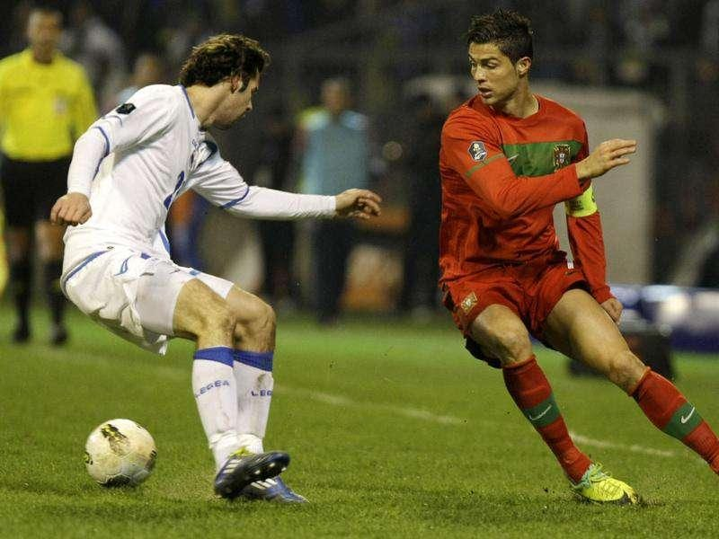 Bosnia's Adnan Zahirovic, left, is challenged by Portugal's Cristiano Ronaldo during their Euro 2012 Group D qualifying soccer match in Zenica, Bosnia.