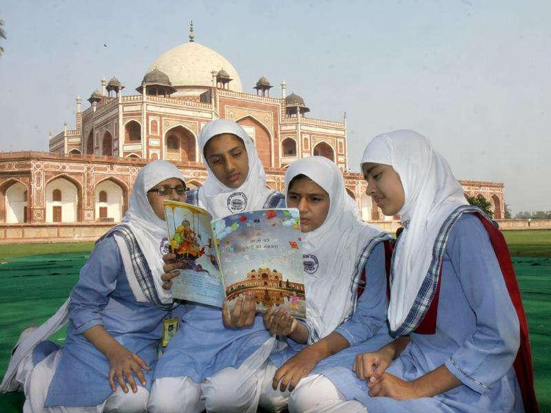 School children go through the book on Humayun Tomb released by cultural minister Kumari Selja to celebrate Children's Day at the Tomb complex.