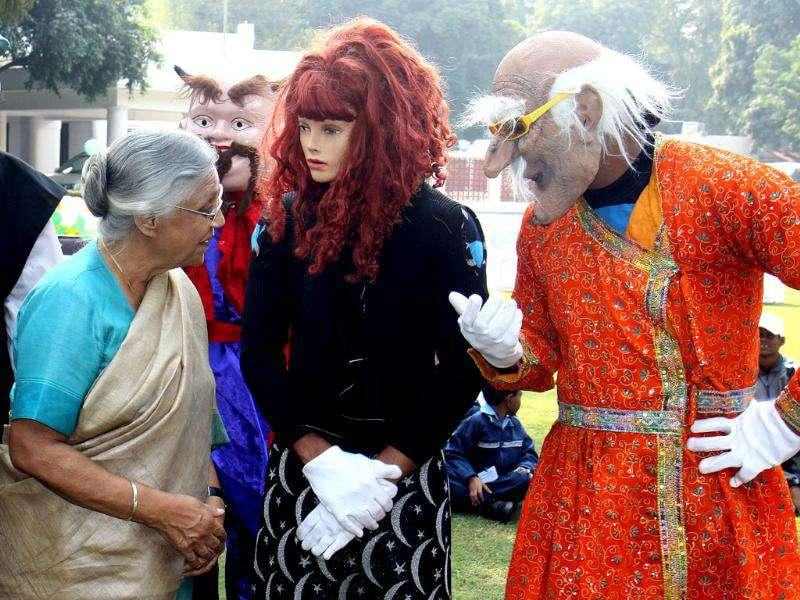 Delhi chief minister Sheila Dikshit talks to artists dressed as cartoon characters to celebrate Children Day's in New Delhi.