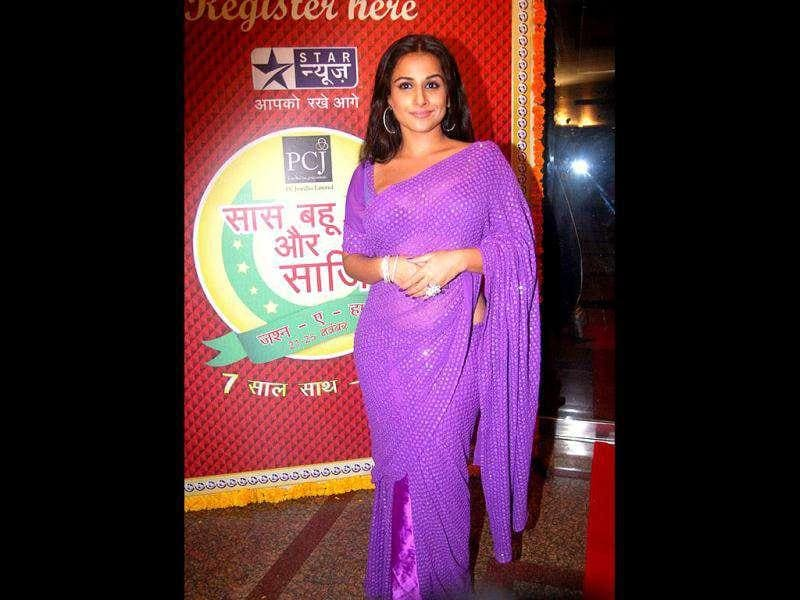 Vidya is clad in a purple shimmering sari.