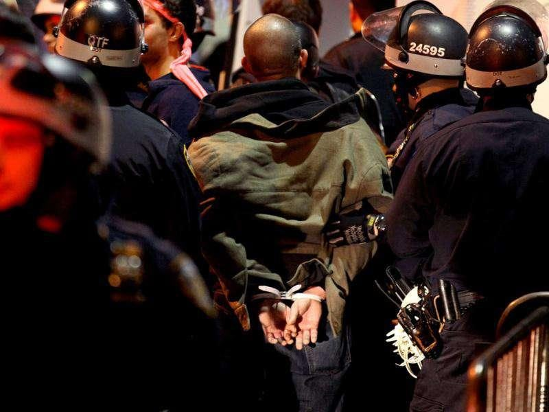 An Occupy Wall Street protester is taken into custody by police after being ordered to leave Zuccotti Park, the longtime encampment in New York.