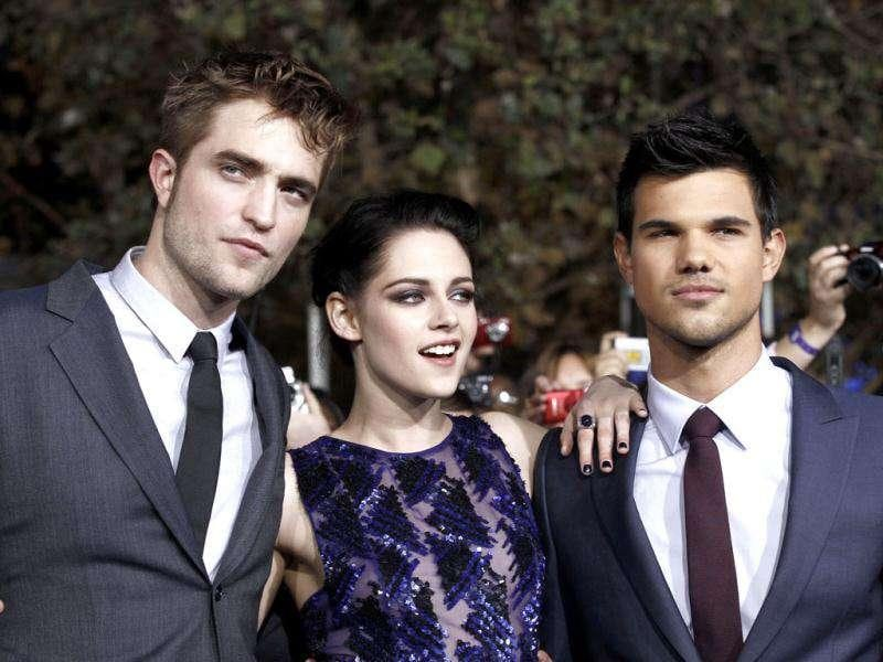 Robert Pattinson, left, Kristen Stewart, center, and Taylor Lautner arrive at the world premiere of The Twilight Saga: Breaking Dawn - Part 1. (AP Photo/Matt Sayles)