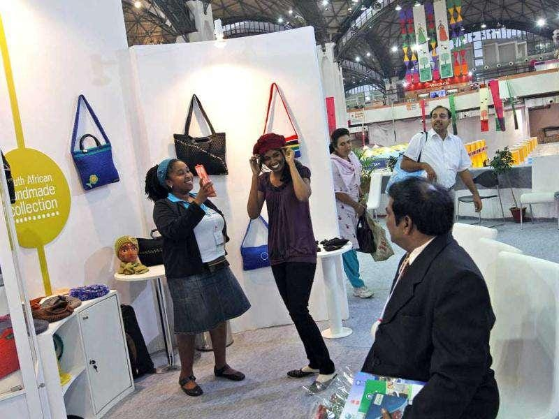 A visitor tries on a cap at the South African stall on the first day of the India International Trade Fair in New Delhi. Photo: AP