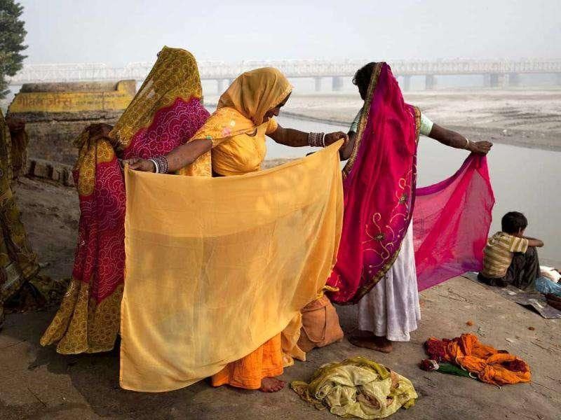 Women arrange their saris after taking a holy dip in the Ganges River at the site of the Sonepur Fair near Patna.