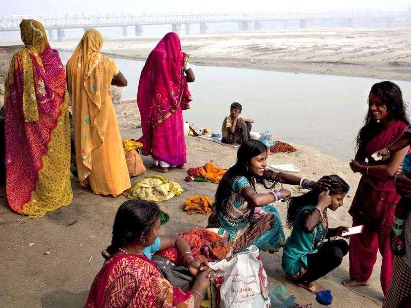 A woman combs the hair of another after taking a holy dip in the Ganges River at the site of the Sonepur Fair near Patna.