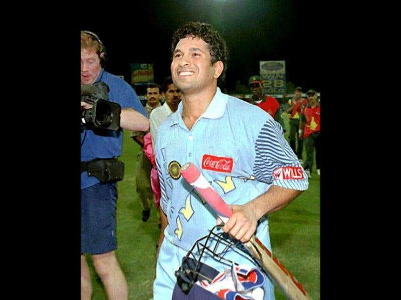 Sachin Tendulkar enjoys a moment of glory after leading his team to victory at the Coca Cola Trophy in Sharjah 13 November. India beat Zimbabwe by 10 wickets in the final of the week-long tournament. Tendulkar scored a century with 6 sixes in the match and was named man-of-the-tournament. AFP PHOTO
