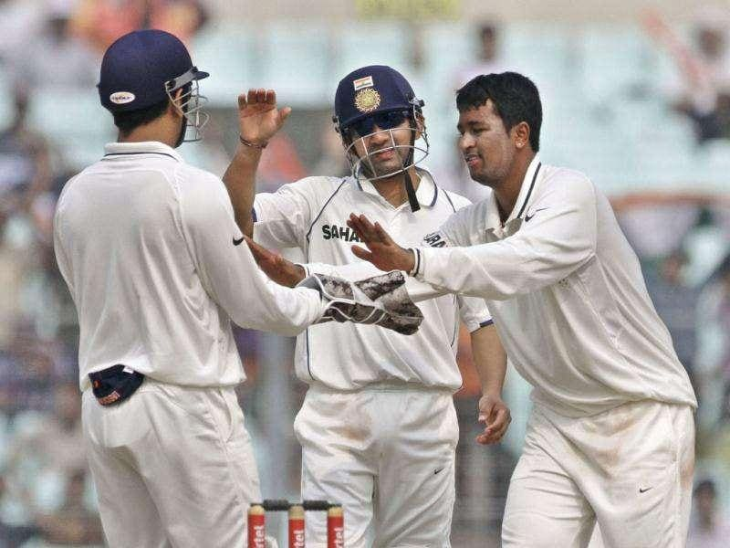 Pragyan Ojha, right, celebrates with teammates Gautam Gambhir, center, and captain Mahendra Singh Dhoni the dismissal of West Indian batsman Darren Sammy during the third day of second cricket Test match again West Indies, in Kolkata.