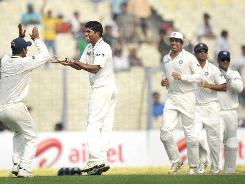Umesh Yadav (2L) with Pragyan Ojha (L) and other teammates celebrate the wicket of Darren Bravo during the third day of the second Test cricket match between Indian and West Indies at the Eden Gardens in Kolkata.