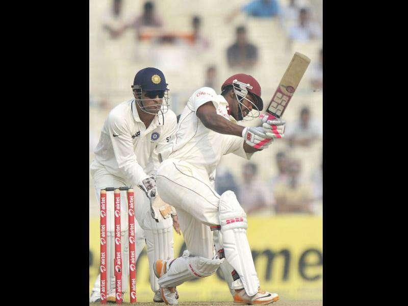 West Indies Darren Bravo plays a shot as Indian captain Mahendra Singh Dhoni looks on during the third day of the second Test cricket match between Indian and West Indies at the Eden Gardens in Kolkata.