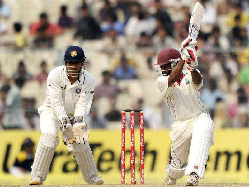 West Indies Adrian Barath plays a shot as Indian captain Mahendra Singh Dhoni looks on during the third day of the second Test cricket match between Indian and West Indies at the Eden Gardens in Kolkata.