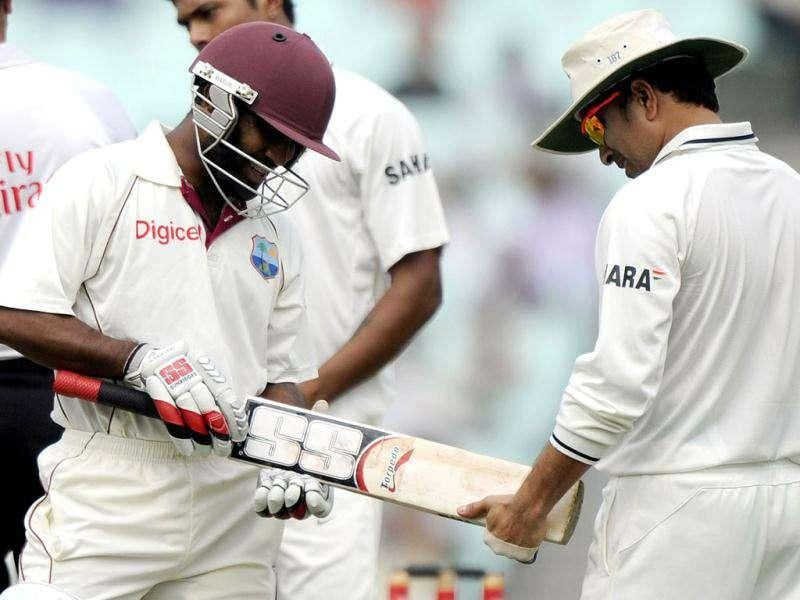 West Indies Adrian Barath shows his bat to Sachin Tendulkar during the third day of the second Test cricket match between Indian and West Indies at the Eden Gardens in Kolkata.