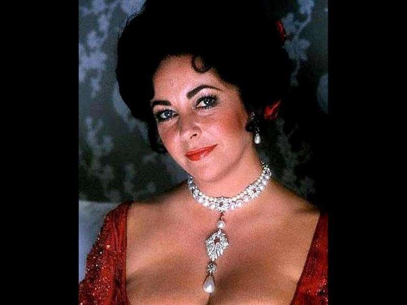 Liz Taylor seen wearing the La Peregrina, a pearl, diamond, ruby and cultured pearl necklace by Cartier.