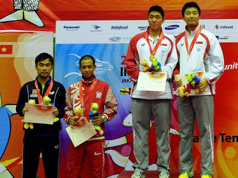 Men's singles table tennis winner Singaporean Gao Ning (2R), runner up compatriot Yang Zi (R), third placed Indonesian Ficky Supit Santoso (2L) and Vietnamese Tran Tuan Quynh (L) pose at the awards podium during the 26th Southeast Asian Games.