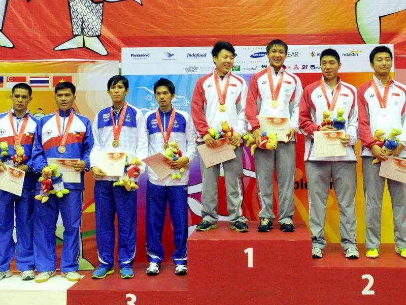 Men's table tennis double winners Singaporean Yang Zi/Sun Bei-bei, runner up compatriots Gao Ning/Feng Tian Wei, third place Richard Gonzales/ Rodel Ireneo Valle of the Philippines, third place Chaisit Chaitat/Nikom Wongsiri of Thailand pose at the awards podium during the 26th Southeast Asian Games.