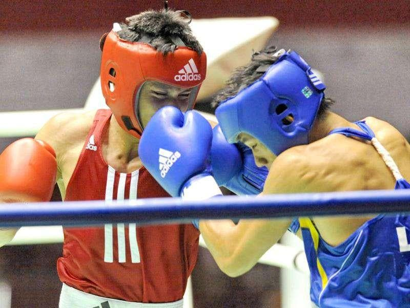 Muhamad Ridwan of Singapore (L) competes with Khammouna Khonavang of Laos in the men's light weight 60kg boxing event at the 26th Southeast Asian Games (SEAGAMES) in Palembang, Sumatra province.