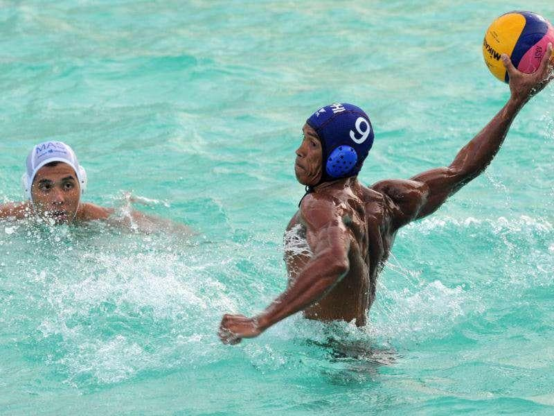Ronald Alamara (R) of Philippines attempts a goal Malaysia in the men's waterpolo at the 26th Southeast Asian Games (SEAGAMES) in Palembang, Sumatra province.