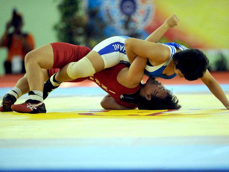 Thongkam Wilaiwen (top) of Thailand wrestles with Eka Setiawati of Indonesia during the women's 59kg wrestling competition at the 26th Southeast Asian Games (SEAGAMES) in Palembang, Sumatra province.