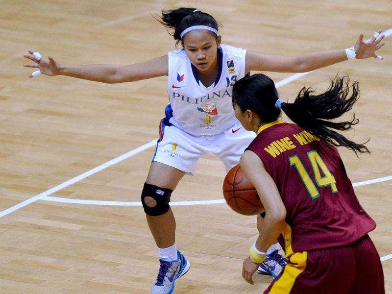 Philippines' Bernadette Mercano (L) tries to block Myanmar's Wine Wine during the women basketball preleminary round games at the 26th Southeast Asian Games (SEAGAMES) in Jakarta.