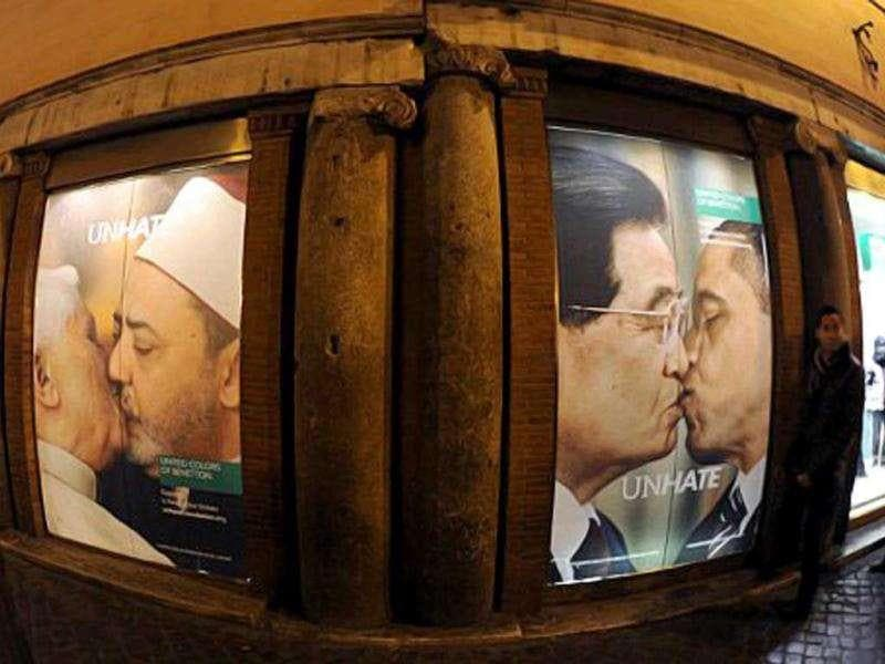 Photo montages of the pope kissing a leading imam (L) and US President Barack Obama smooching his Chinese counterpart Hu Jintao (R) that was part of a new global ad campaign. People look at photo montages of the new ad campaign of Italian clothing company Benetton in their shop in front of the Trevi fountain in Rome.