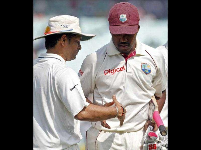 Sachin Tendulkar congratulates West Indies' Darren Bravo for his century on the fourth day of their second cricket Test match in Kolkata.