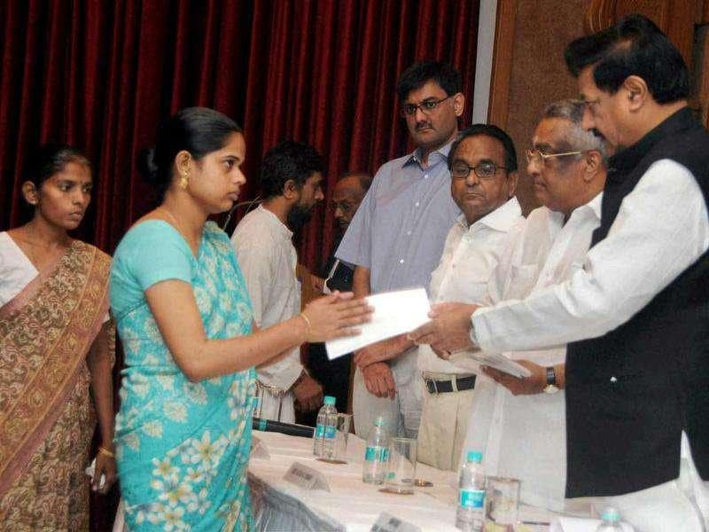 Chief Minister of Maharashtra Prithviraj Chavan gives away cheques as financial assistance to the relatives of Opera House bomb blast victims on behalf of the Gem and Jewellery National Relief foundation, at a function in Mumbai.