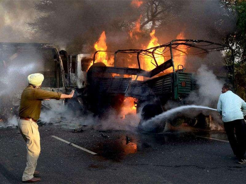 Firemen douse the fire after a head-on collision between a bus carrying the Indian Women's Kabaddi team and an Army truck at cantonment road in Bathinda.