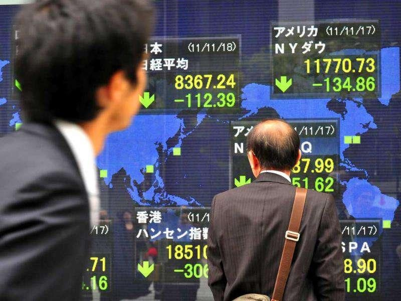 Businessmen gaze at a share prices board in Tokyo. Japan's share prices fell 112.39 points to close at 8,367.24 points at the morning session of the Tokyo Stock Exchange.